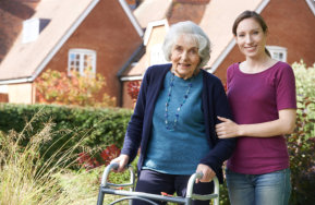 caregiver helping senior woman to walk