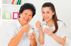 caregiver and a senior woman drinking milk