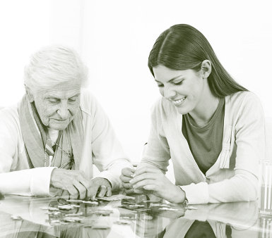 caregiver and a senior woman playing puzzle