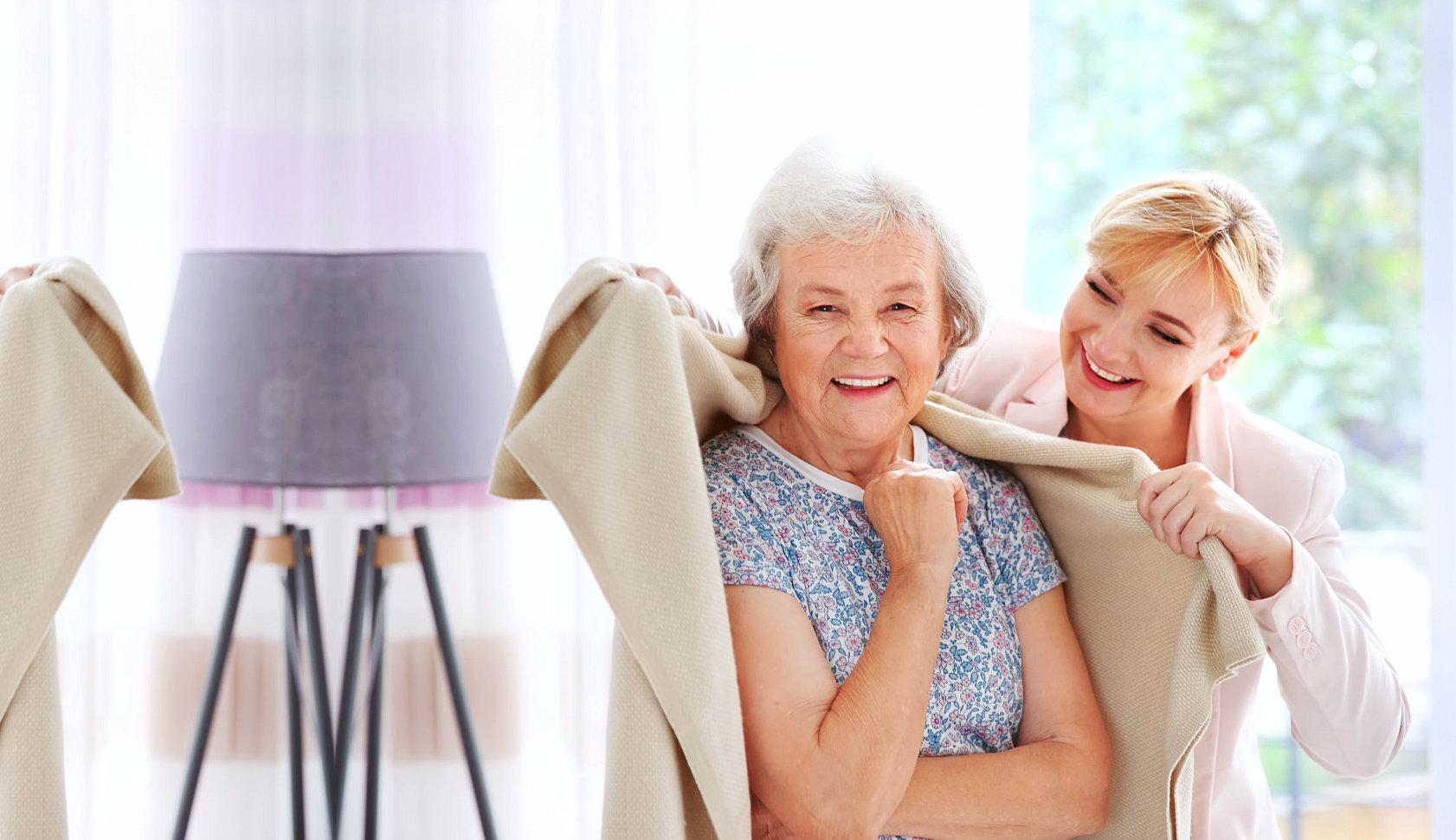 caregiver giving towel to a senior woman