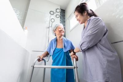 caregiver helping senior woman taking a shower