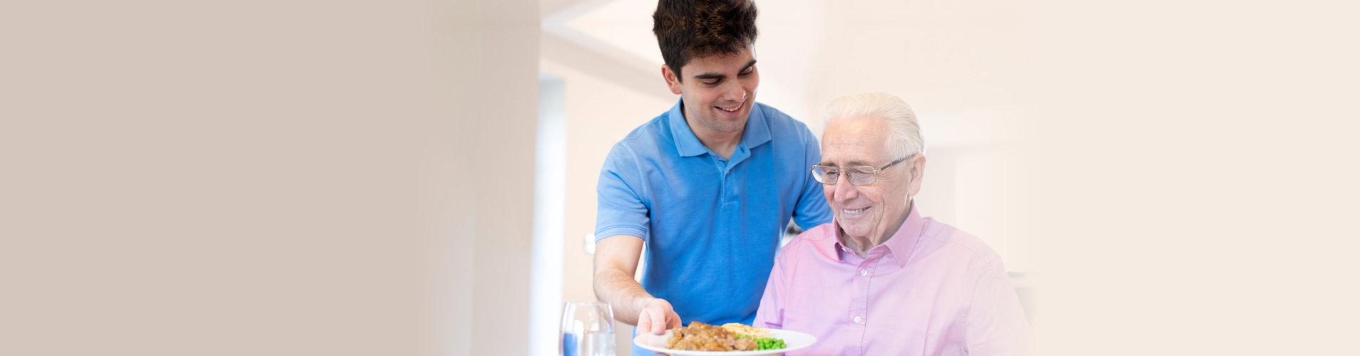 male caregiver serving meal to senior man