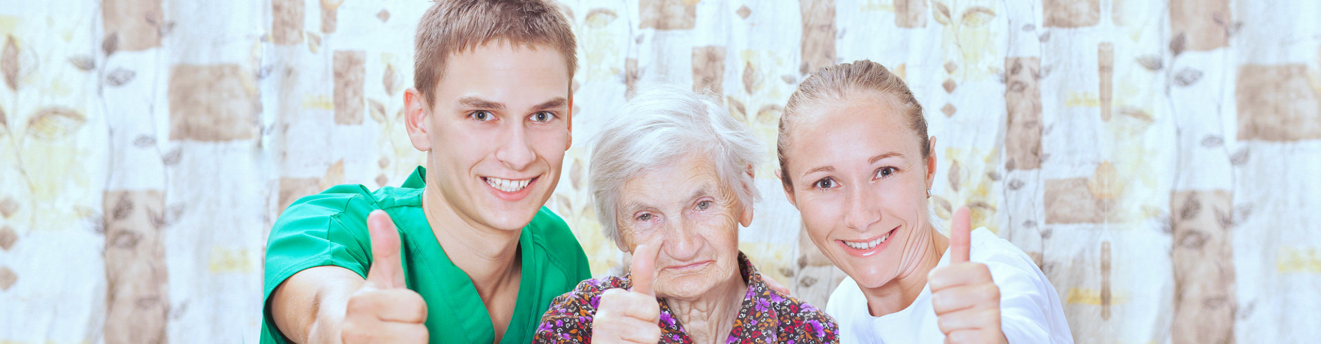 two caregiver and a senior woman giving a thumbs up